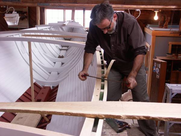 Amon using a draw knife to build a boat