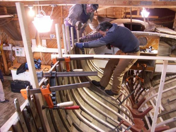 Pulling the ribs in place for a new boat built the traditional way
