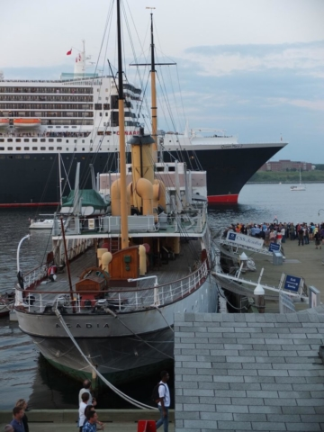 Crowds gather to watch the Cunnard Line's Queen Mary sail past the CSS Acadia