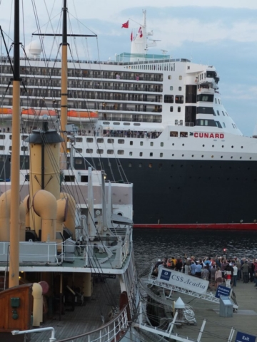 The past meets the present as the Cunard Line's Queen Mary sails past the CSS Acadia